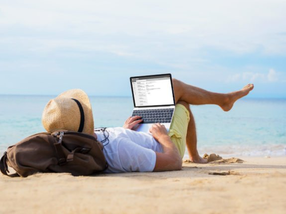 Man,Reading,Email,On,Laptop,While,Relaxing,On,Beach